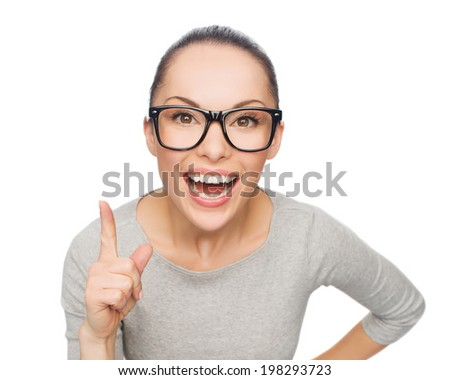 happiness and gesture concept - smiling asian woman in eyeglasses with finger up - stock photo
