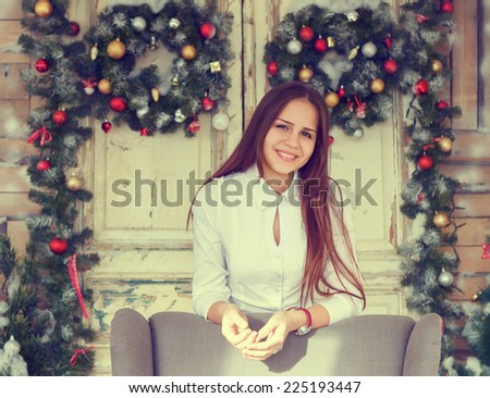 Happiness and holidays concept. Smiling teenage girl having fun over christmas decoration background - stock photo
