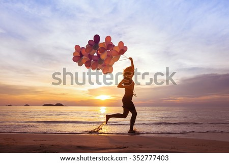 happiness and inspiration concept, psychology of happy people, young woman running with multicolored balloons on the beach - stock photo