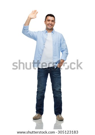 happiness and people concept - smiling man in shirt and jeans waving hand - stock photo