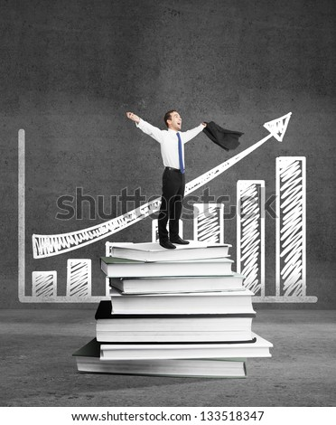 happiness businessman standing on books and drawing chart - stock photo
