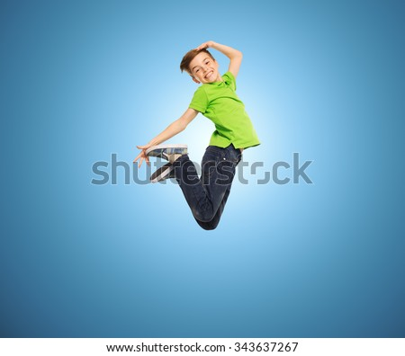 happiness, childhood, freedom, movement and people concept - smiling boy jumping in air over blue background - stock photo