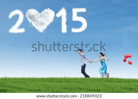 Happiness couple holding hands and balloon on meadow with heart shaped cloud number 2015 - stock photo