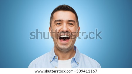 happiness, emotions and people concept - laughing man over blue background - stock photo