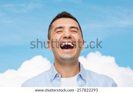 happiness, emotions and people concept - laughing man over blue sky and cloud background - stock photo