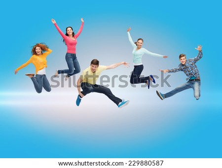 happiness, freedom, friendship, movement and people concept - group of smiling teenagers jumping in air over blue laser background - stock photo