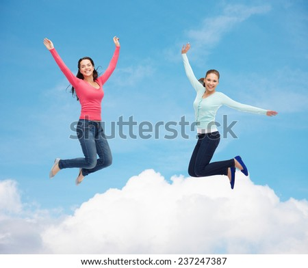 happiness, freedom, friendship, movement and people concept - smiling young women jumping in air over blue sky with white cloud background - stock photo