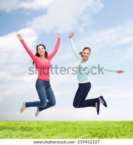happiness, freedom, friendship, movement, summer and people concept - smiling young women jumping in air over natural background - stock photo