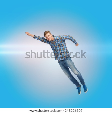 happiness, freedom, movement and people concept - smiling young man flying in air over blue background with laser light - stock photo