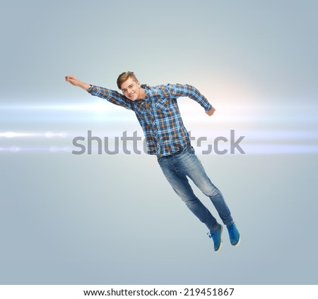 happiness, freedom, movement and people concept - smiling young man flying in air over gray background with laser light - stock photo
