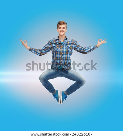 happiness, freedom, movement and people concept - smiling young man hanging of flying in air over blue laser background - stock photo