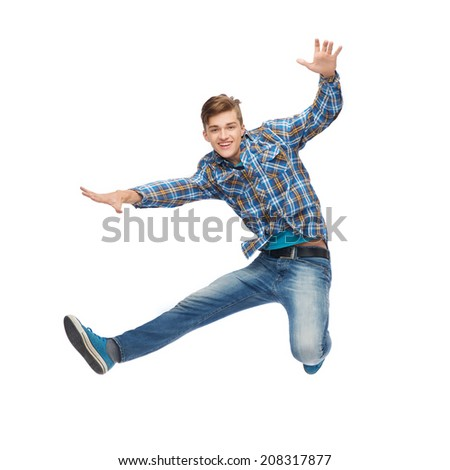 happiness, freedom, movement and people concept - smiling young man jumping in air - stock photo