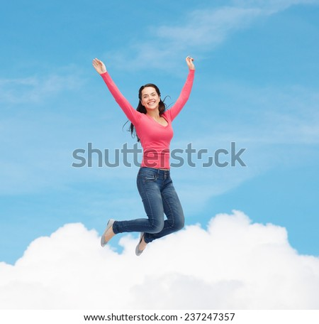 happiness, freedom, movement and people concept - smiling young woman jumping in air over blue sky with white cloud background - stock photo
