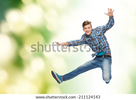 happiness, freedom, movement, ecology and people concept - smiling young man jumping in air over green background - stock photo