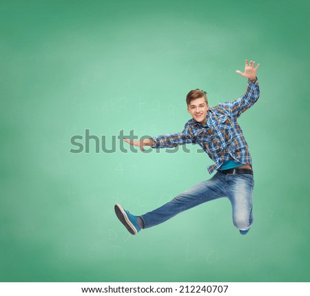 happiness, freedom, movement, education and people concept - smiling young man jumping in air over over green board background - stock photo