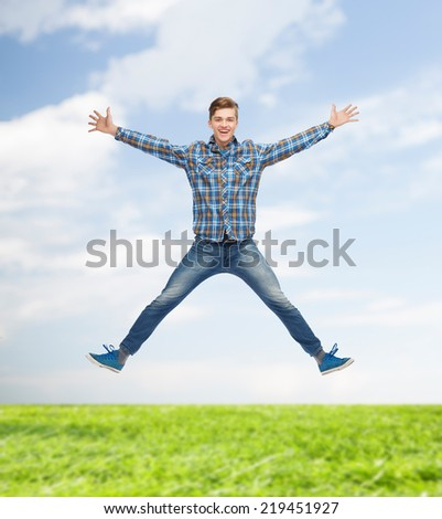 happiness, freedom, vacation, summer and people concept - smiling young man jumping in air over natural background - stock photo
