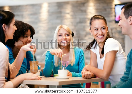 Happiness friends enjoying coffee together in modern  cafe - stock photo