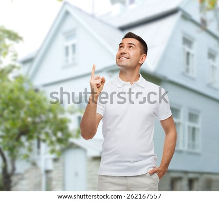 happiness, gesture and people concept - smiling man pointing finger up over house background - stock photo
