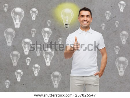 happiness, gesture and people concept - smiling man showing thumbs up over gray background with lighting bulbs - stock photo