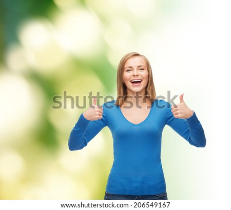happiness, gesture and people concept - smiling young woman in casual clothes showing thumbs up - stock photo