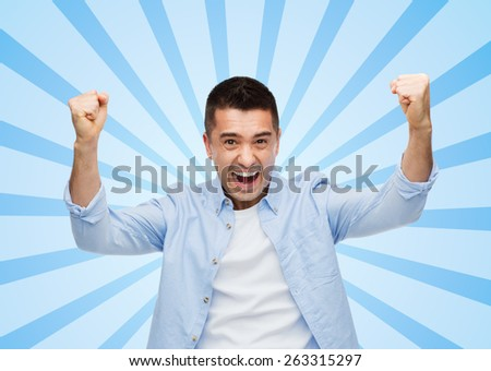 happiness, gesture, emotions and people concept - happy laughing man with raised hands blue burst rays background - stock photo