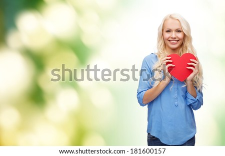 happiness, health and love concept - smiling woman with red heart - stock photo