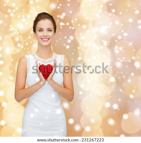 happiness, health, charity and love concept - smiling woman in white dress with red heart over beige background over beige lights background and snow - stock photo