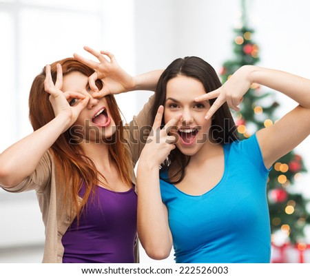 happiness, holidays, friendship and people concept - smiling teenage girls having fun over living room and christmas tree background - stock photo