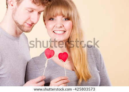 Happiness in love. Lovely charming couple smiling. Happy joyful woman and man holding little hearts on sticks. Two people with sign symbol of good relationship feelings. - stock photo