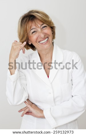 Happiness mature female pharmacist smiling and  making call me gesture.  - stock photo