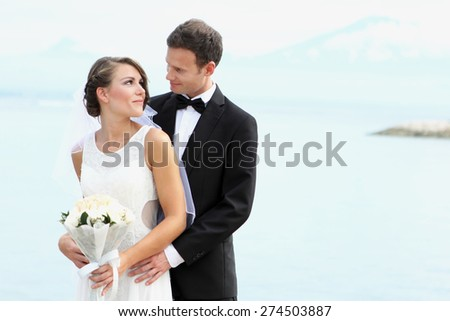 happiness of young newlywed couple with beach on the background - stock photo