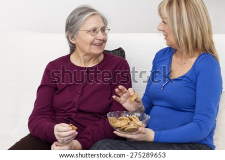 Happiness senior woman friendly chatting with her mature nurse and eating a biscuits. . - stock photo