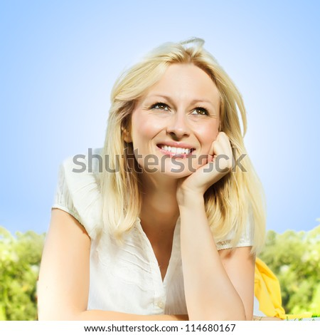 Happiness smiling blonde woman relaxing on green grass in the park, against clear blue sky . - stock photo