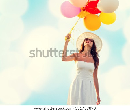 happiness, summer, holidays and people concept - smiling young woman wearing sunglasses with balloons over blue lights background - stock photo