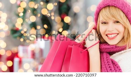 happiness, winter holidays and people concept - smiling young woman in hat and scarf with pink shopping bags over christmas tree background - stock photo