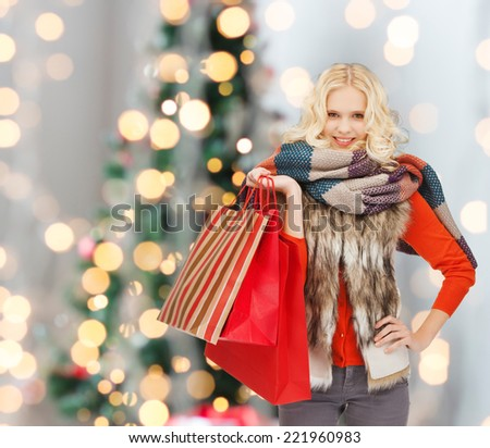 happiness, winter holidays and people concept - smiling young woman in winter clothes with red shopping bags over christmas tree background - stock photo
