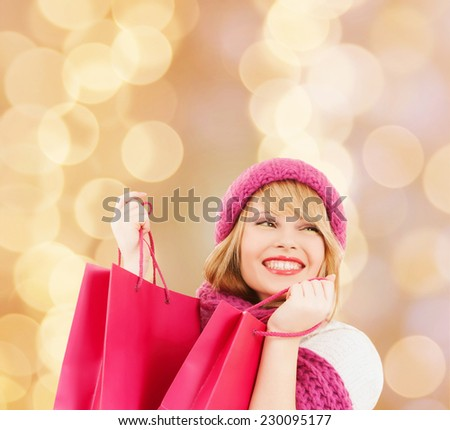 happiness, winter holidays, christmas and people concept - smiling young woman in hat and scarf with pink shopping bags over beige lights background - stock photo