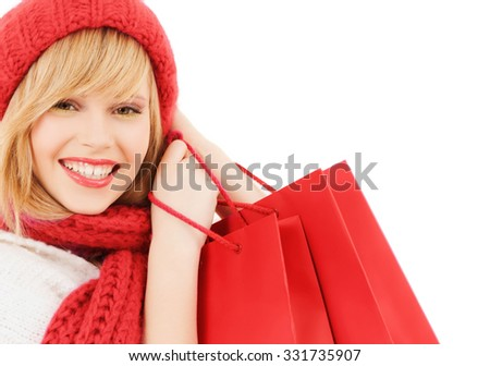 happiness, winter holidays, christmas and people concept - smiling young woman in hat and scarf with red shopping bags over white background - stock photo