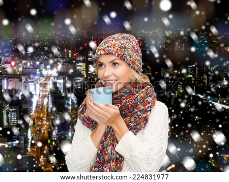 happiness, winter holidays, christmas, beverages and people concept - smiling young woman in warm clothes with cup over snowy city background - stock photo