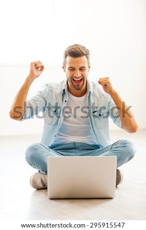 Happiness without limits. Excited young man working gesturing and looking at laptop while sitting on the floor at his apartment - stock photo
