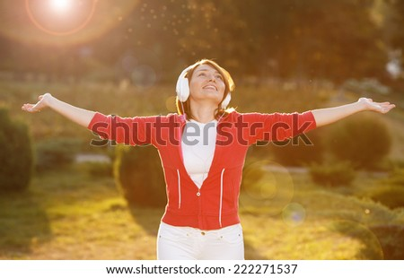 Happiness woman enjoy nature. Beauty girl on the street. The concept of freedom. Beauty girl under the sky and the sun's rays. Pleasure. Woman with headphones listening to music on her head. - stock photo