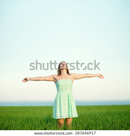 Happiness woman stay outdoor under sunlight of sunset. With raised hands at the sunrise time. - stock photo