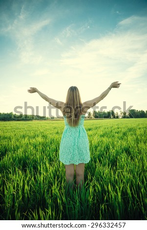 Happiness woman stay outdoor under sunlight of sunset. With raised hands at the sunrise time - stock photo