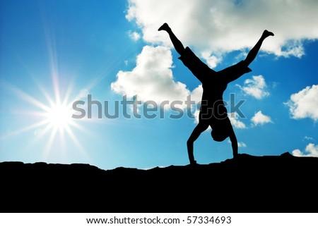Happy acrobat on the sunset. Emotional scene. - stock photo