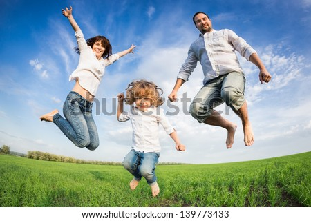 Happy active family jumping in green field against blue sky. Summer vacation concept - stock photo