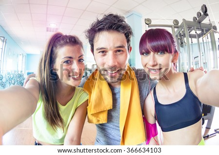 Happy active friends trio taking selfie in gym training studio center - Sporty people ready for fitness time - Healthy lifestyle and sport concept - Soft bright cyan marsala desaturated filtered look - stock photo