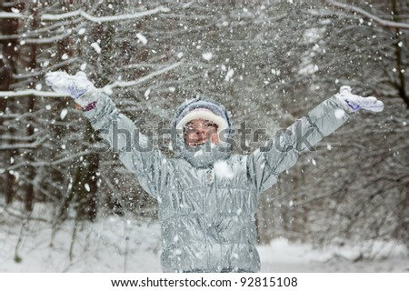 Happy active girl having fun and throwing snow in winter forest - stock photo