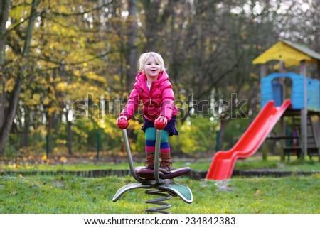 Happy active little child, blonde curly toddler girl, wearing beautiful red warm jacket, having fun at playground in the park on sunny day - stock photo