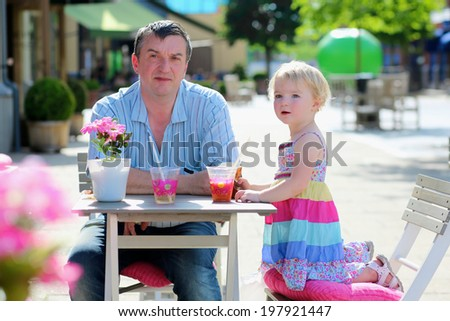 Happy active man relaxing together with his little daughter, adorable blonde toddler girl, in cozy outdoors cafe drinking ice tea and fresh smoothie on a hot summer day - father and child concept - stock photo