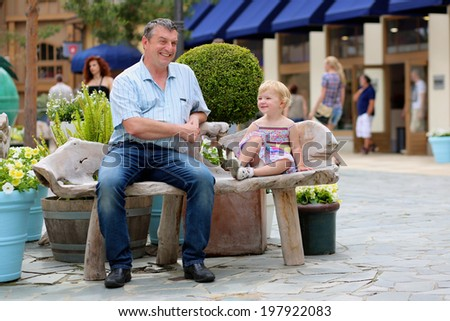 Happy active man relaxing together with his little daughter, adorable blonde toddler girl, sitting on wooden bench in middle of outlet shopping street during summer sales - father and child concept - stock photo